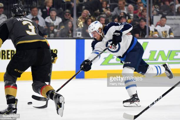 Patrik Laine of the Winnipeg Jets takes a shot as Brayden McNabb of the Vegas Golden Knights defends during the first period in Game Four of the...