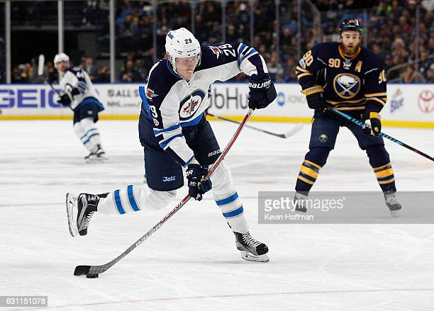 Patrik Laine of the Winnipeg Jets takes a shot as Ryan O'Reilly of the Buffalo Sabres looks on during the first period at the KeyBank Center on...