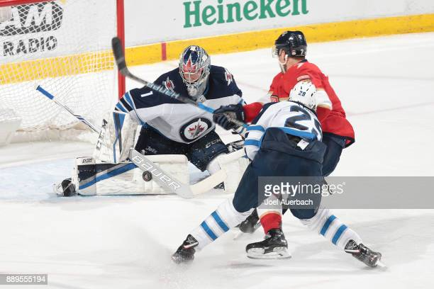 Patrik Laine of the Winnipeg Jets trails Colton Sceviour of the Florida Panthers as Goaltender Eric Comrie stops his shot at the BBT Center on...