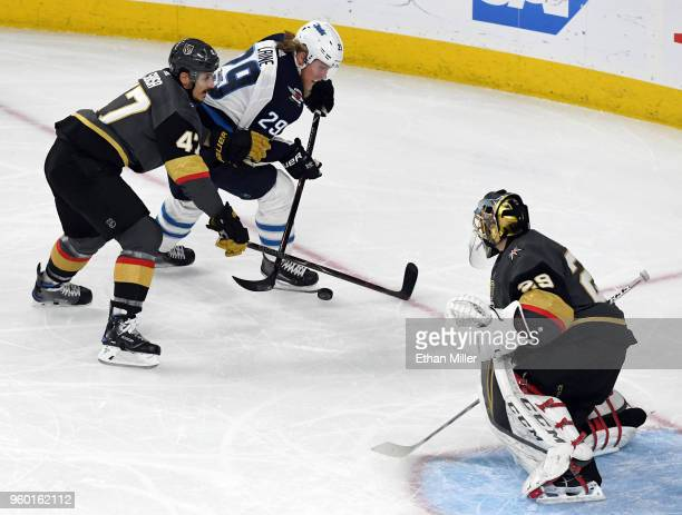Patrik Laine of the Winnipeg Jets tries to get a shot off on MarcAndre Fleury of the Vegas Golden Knights under pressure from Luca Sbisa of the...