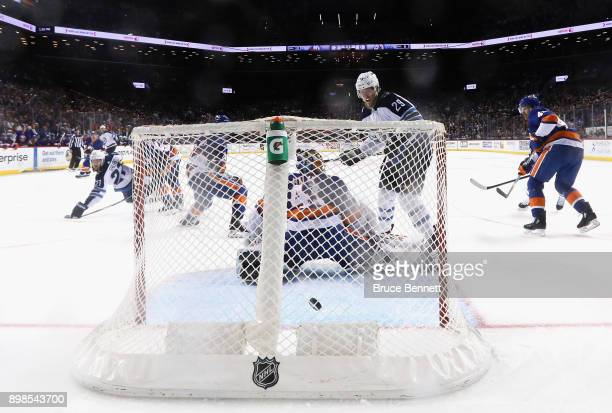 Patrik Laine of the Winnipeg Jets watches the first NHL goal go into the net for Tucker Poolman of the Winnipeg Jets against the New York Islanders...