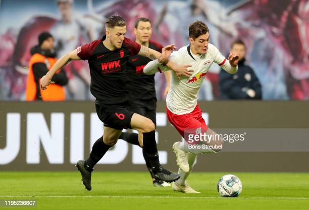 Patrik Schick of RB Leipzig battles for possession with Jeffrey Gouweleeuw of FC Augsburg during the Bundesliga match between RB Leipzig and FC...