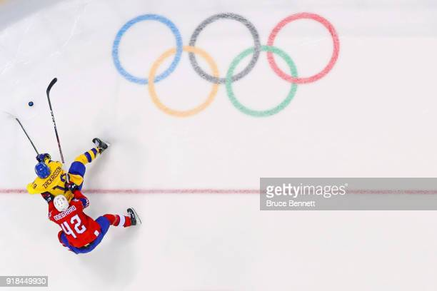Patrik Zackrisson of Sweden is challenged by Henrik Odegaard of Norway during the Men's Ice Hockey Preliminary Round Group C game between Norway and...