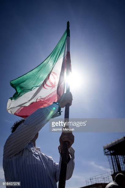 Patriot man holding Iranian flag against sun