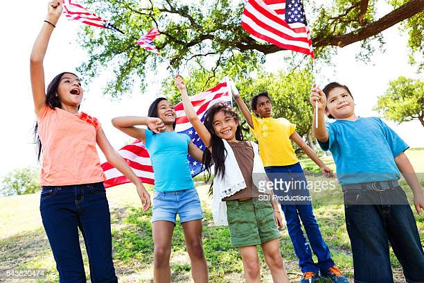 Patriotic friends wave flags at a parade