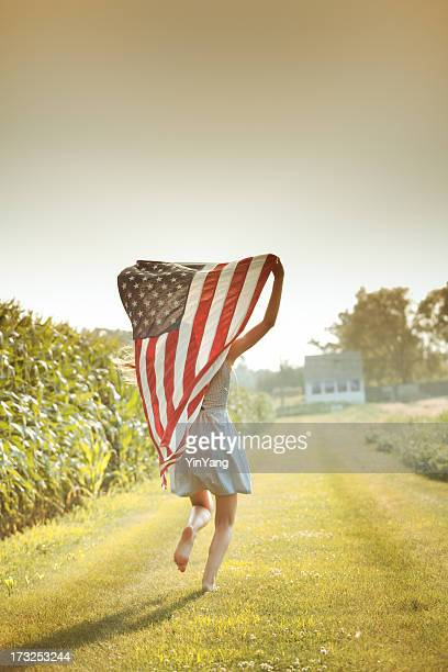patriotic girl flying american flag, usa fourth of july banner - fourth of july stock pictures, royalty-free photos & images