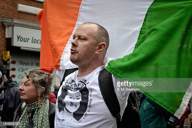 Patriotic Irish Republican man holding up the Tri-Colour Irish flag wearing a t-shirt of the iconic Sex Pistols single, 'God Save the Queen'. On the...