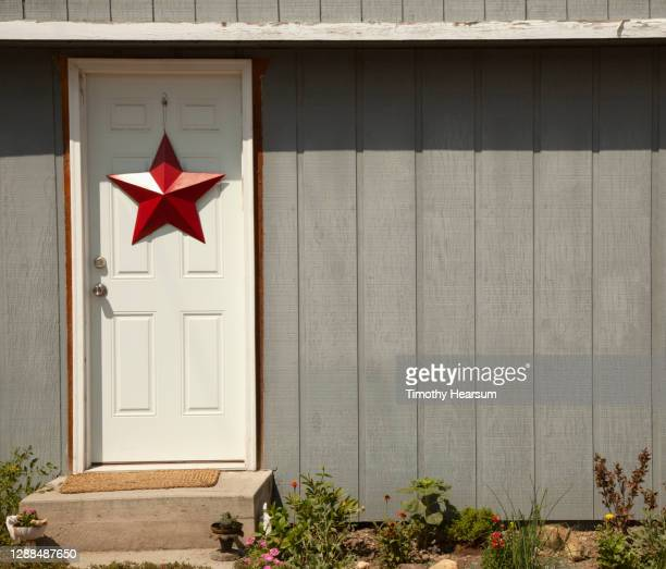 patriotic red star on a white front door of a house - timothy hearsum stock pictures, royalty-free photos & images
