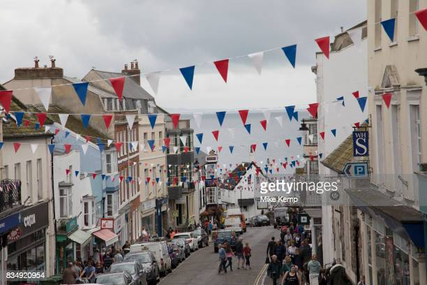 Patriotic red white and blue bunting stretched out over Broad Street in Lyme Regis, Dorset, England, United Kingdom. Lyme Regis is a coastal town in...