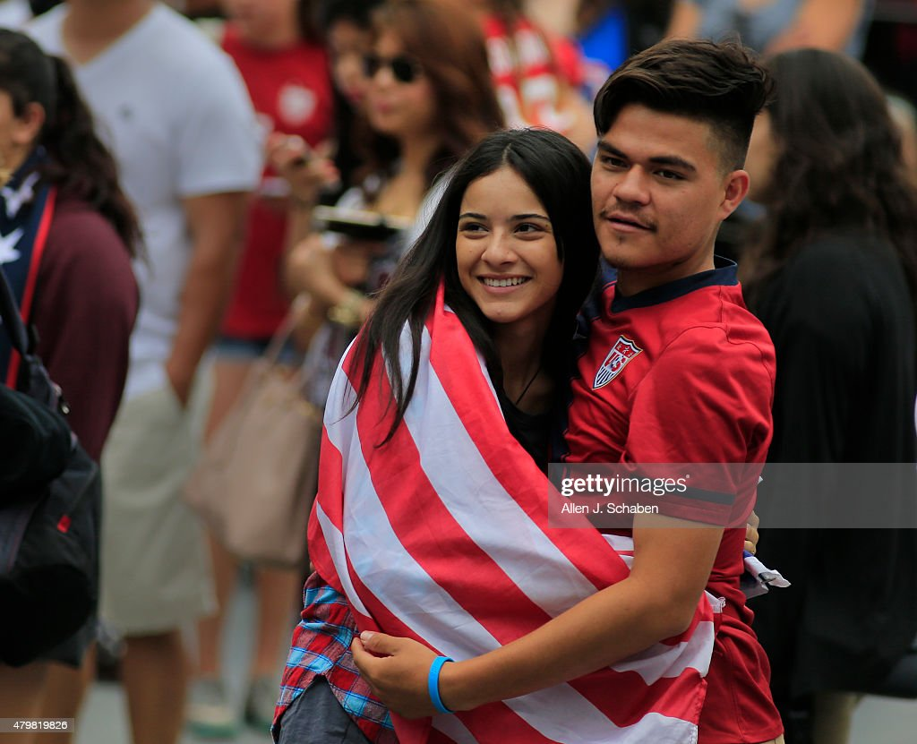 Patriotic soccer fans wrap up in an American flag as the 2015 United States Women's National Soccer Team takes the stage after winning the FIFA Women's World Cup at a free, public championship celebration at L.A. Live's Microsoft Square in Los Angeles, Calif., on July 7, 2015.
