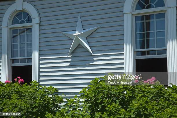 patriotic star on the clapboard facade of a house - timothy hearsum stock pictures, royalty-free photos & images
