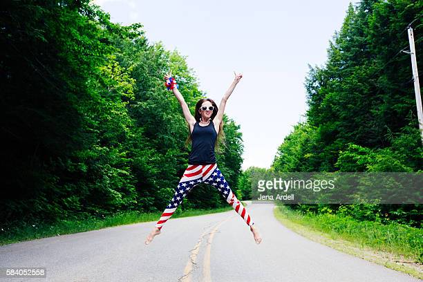 patriotic woman jumping in middle of street - july stock pictures, royalty-free photos & images