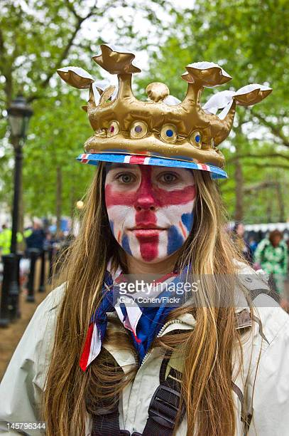 A patriotically painted wellwisher braves inclement weather to show her support for Queen Elizabeth II on the ceremonila procession day of her...
