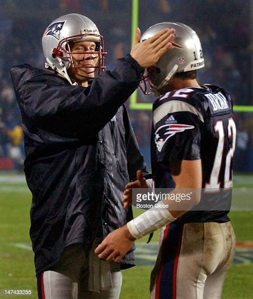Patriots backup quarterback Drew Bledsoe left gives starting signal caller Tom Brady a pat on the head following a fourth quarter New England...