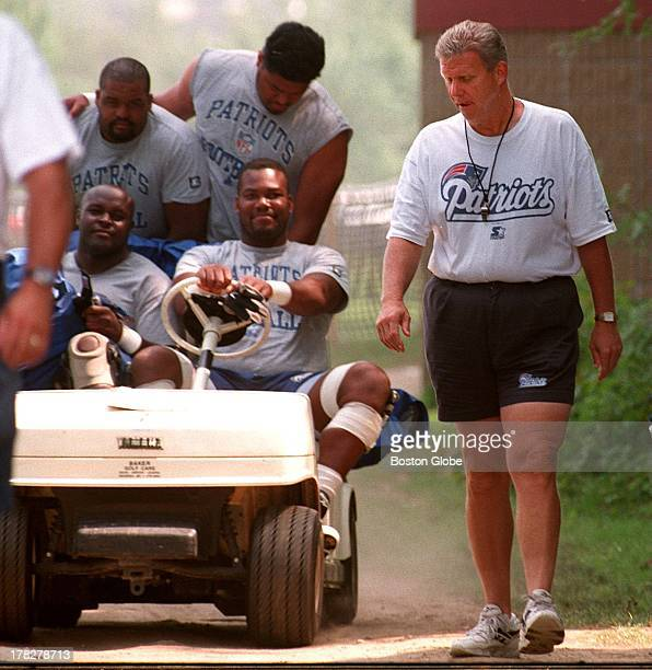 Patriots coach Bill Parcells walks while his players take the cart to practice