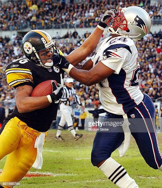 Patriots cornerback Ty Law right and Steelers wide receiver Hines Ward each have the other's face mask grabbed as Law tries to force Hines out of...