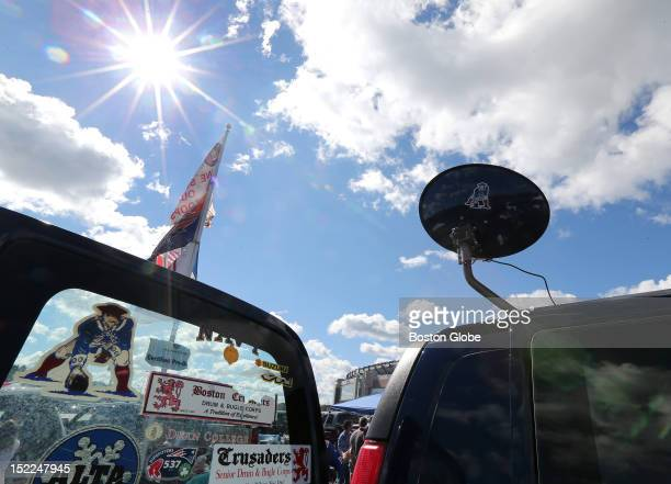 Patriots logos and flags fly in the parking lot at Patriot Place as fans tailgate before the New England Patriots play the Arizona Cardinals at...