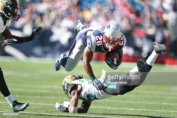Patriots player James White flies over Jaguars player Demetrius McCray in the fourth quarter as the New England Patriots hosted the Jacksonville...