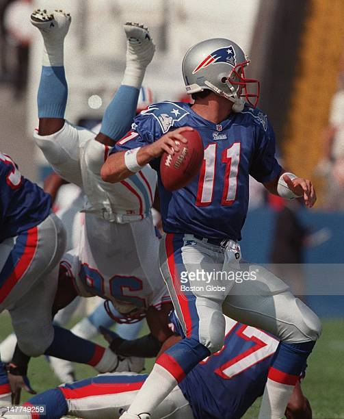 Patriots quarterback Drew Bledsoe drops back to pass and he gets some good protection as Oilers linebacker Joe Bowden is sent head over heels by the...