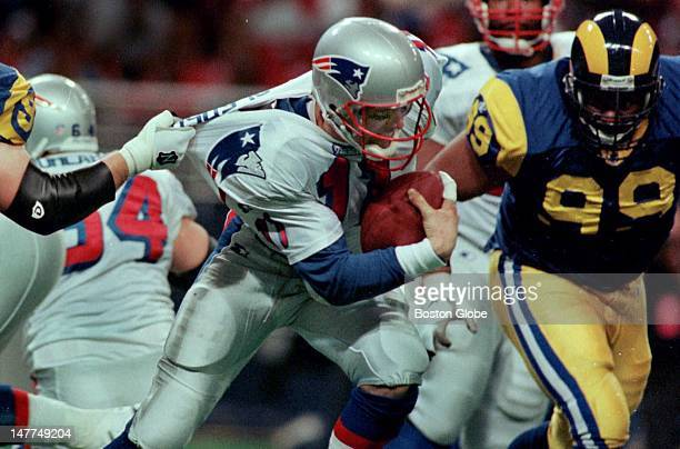 Patriots quarterback Drew Bledsoe has his shirt practically ripped off of his back as he is sacked in the second half by the Rams defense in St Louis...