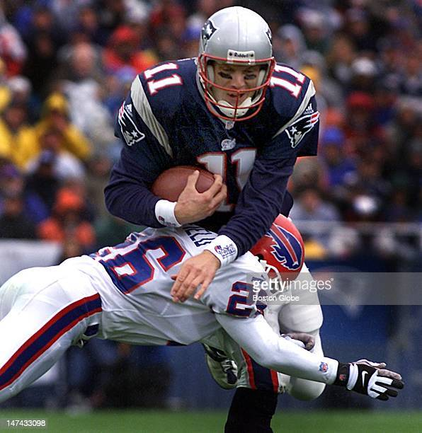 Patriots quarterback Drew Bledsoe is brought down by the Bills cornerback Antoine Winfield after a short scramble first quarter action