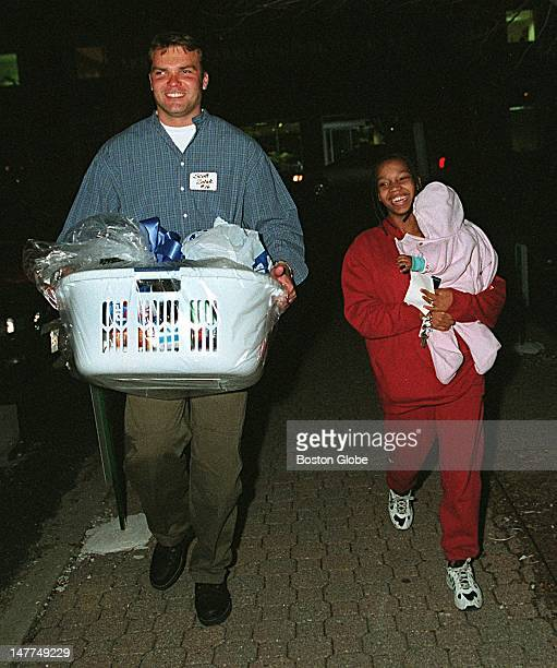 Patriots quarterback Scott Zolak helps Nicole Milton of Dorchester who is carrying her daughter Cierra 6 months old out to her car with the...