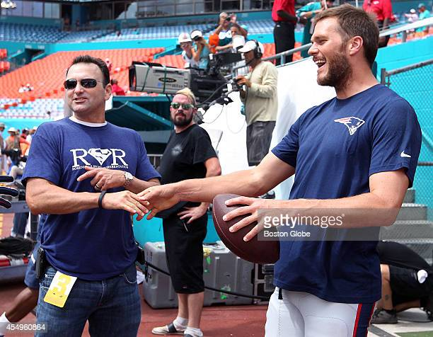 Patriots quarterback Tom Brady says hello to player agent Drew Rosenhaus, left, as he leaves the field after some pre- game warmups. The New England...