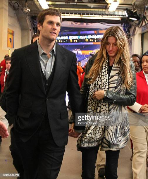Patriots quarterback Tom Brady walks from a press conference at the end of the Super Bowl with wife Giselle