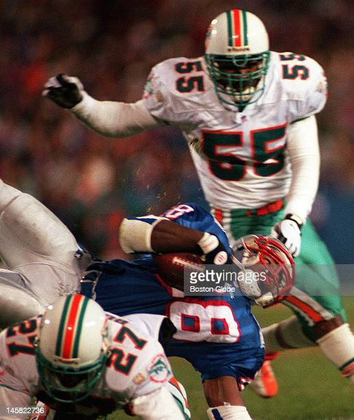 Patriots running back Curtis Martin fights for yardage through Dolphins Terrell Buckley and Chris Singleton