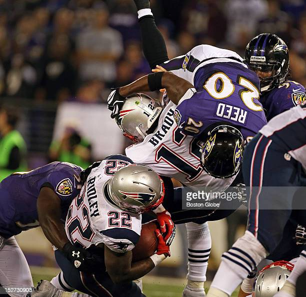 Patriots running back Stevan Ridley is taken down on a third down running play as the Ravens' Ed Reed sails over Patriots quarterback Tom Brady as he...