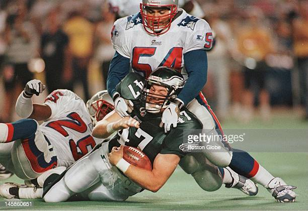 Patriots Tedy Bruschi and Larry Whigham take down Eagles Chad Lewis in first quarter action at Veterans stadium in Philadelphia on Thursday Aug 21...