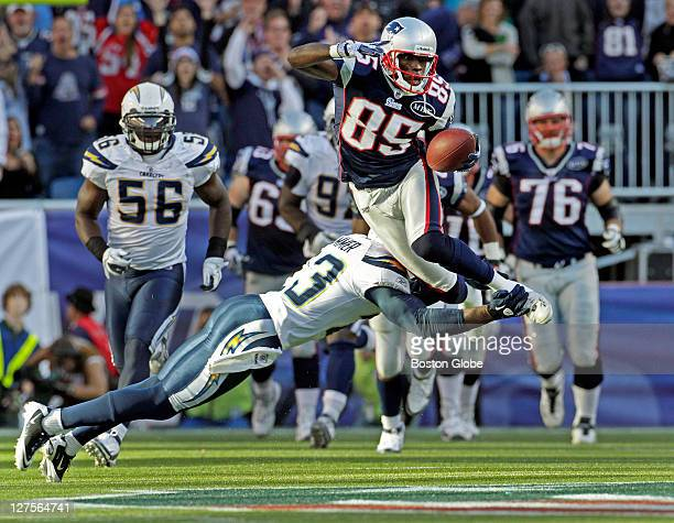 Patriots wide receiver Chad Ochocinco leaps over the tackle attempt of the Chargers Quentin Jammer as he gains 30 yards on a second quarter pass play...