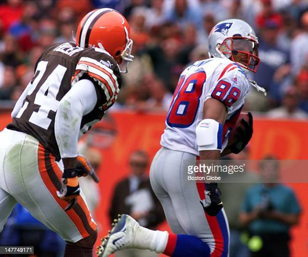 Patriots wide receiver Terry Glenn glances back as he gallops to the end zone after hauling in Drew Bledsoe's fourth quarter pass Browns DB Corey...