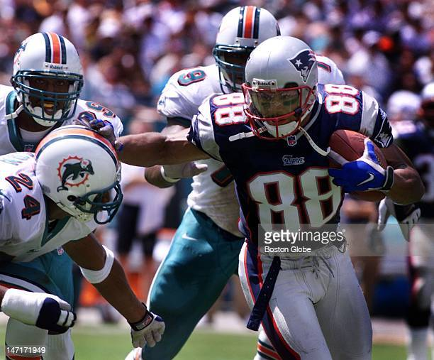 Patriots wide receiver Terry Glenn stiff arms Dolphins cornerback Jerry Wilson as he gains ground after making a catch of a Drew Bledsoe pass