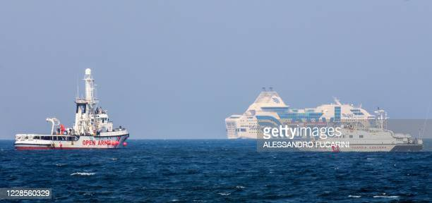 Patrol boat of the Italian Coast Guards sails past the rescue vessel of Spanish NGO Open Arms on September 17, 2020 off the port of Palermo, Sicily,...