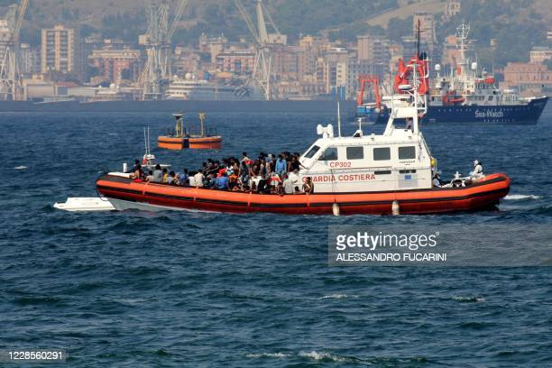 Patrol boat of the Italian Coast Guards transports migrants towards the port of Palermo, Sicily, on September 17, 2020 after they rescued them at sea...