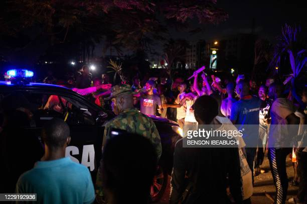 Patrol car of the Lagos State Security drives through Nigerian protesters demonstrating in the streets of Alausa Ikeja on October 20, 2020 after the...