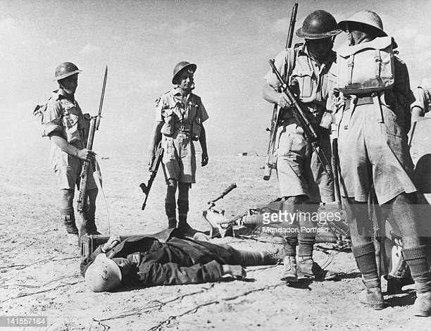 A patrol of English soldiers collecting weapons that have been left behind in a captured position in front of one of the fallen Afrika Korps El...