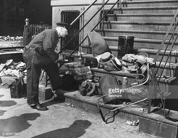 Patrolman George Hughes lists variety of junk removed from the crumbling old brownstone home at Fifth Avenue and 128th Street as the police search...
