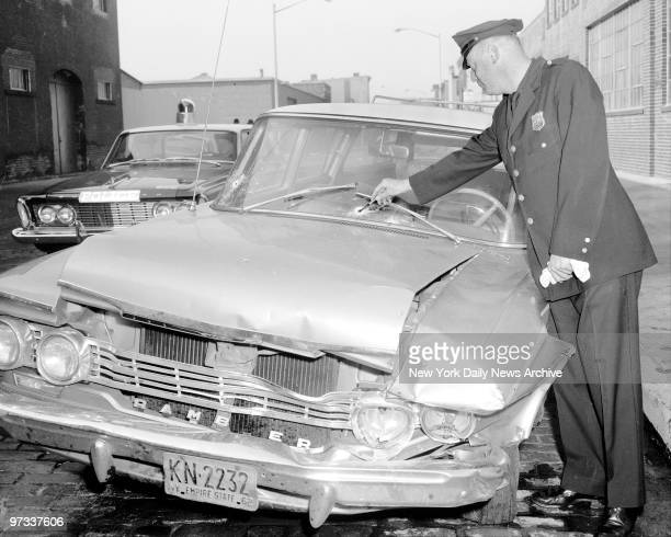 Patrolman James Gannon points out bullet hold in windshield and hood of car Wounded in the hail of shots were Alphonse D'Ambrosio and Carmine Persico...