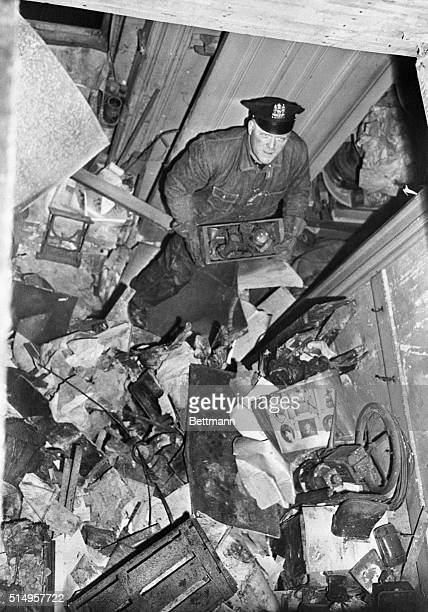 Patrolman John McLaughlin checks through the mess of junk found inside the Collyer mansion at 128th Street and Fifth Avenue as the police continued...