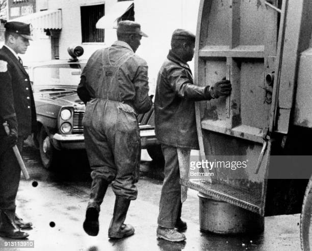 Patrolman KN Overall watches at left as two nonstriking sanitation workers work to keep the downtown area clean Striking workers ignored an ultimatum...
