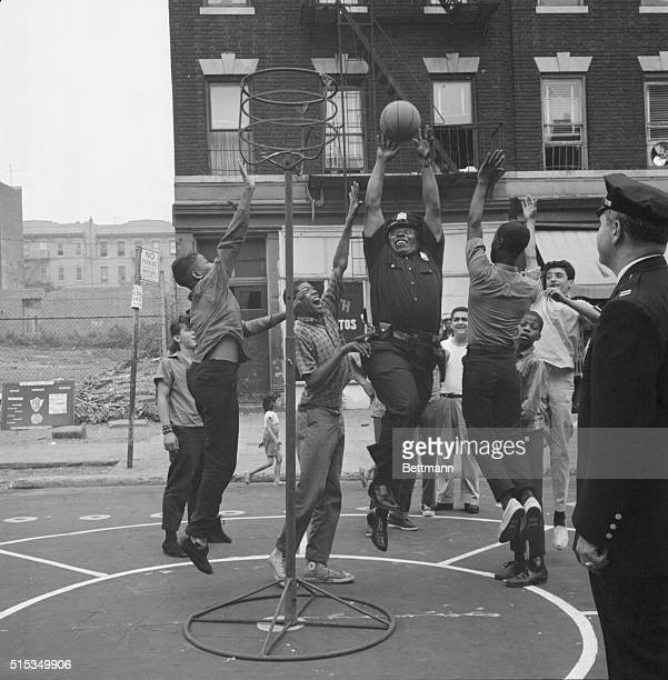 Patrolman Russell Blair of Brooklyn's 73rd Precinct shows the kids how to do it as he leaps for the ball at Sterling Place playstreet August 1st The...