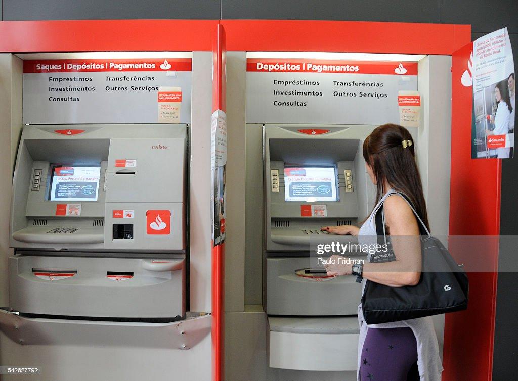 A patron does their banking at an ATM at a Banco Santander