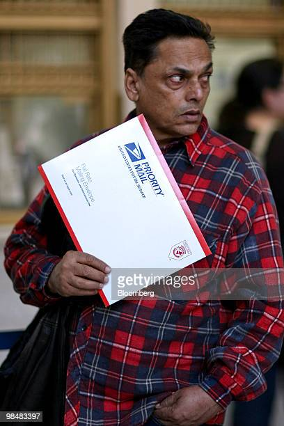 A patron holds a Priority Mail envelope while standing in line at the US Postal Service James A Farley Post Office in New York US on Thursday April...