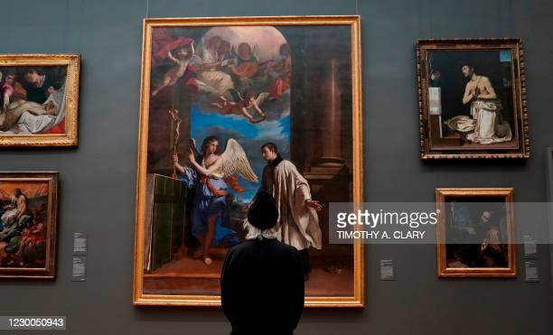 """Patron looks at paintings on display during a press viewing of """"A New Look at Old Masters"""" a newly installed gallery for European Paintings, on..."""