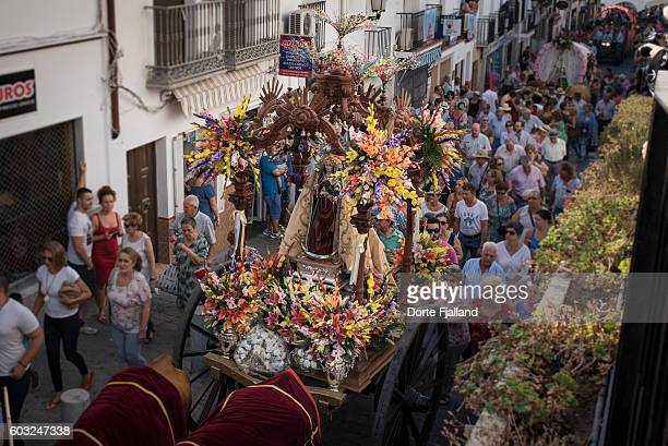 Patron of the village being carried on a throne the a street in an Andalusian village