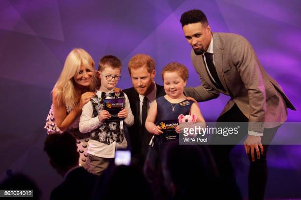 Patron of WellChild Prince Harry poses for a photograph after presenting awards to Finley Green second left aged 7 and Erin Cross aged 7 with hosts...