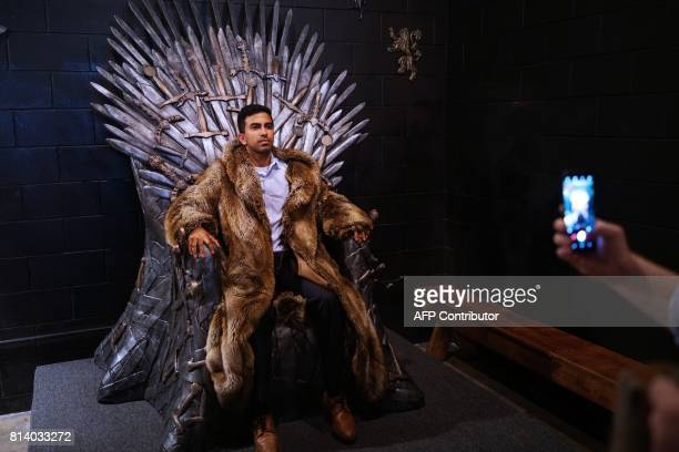 A patron poses for a photo on the Iron Throne at the Game of Thrones popup bar in Washington DC on July 12 2017 As Game of Thrones returns for its...