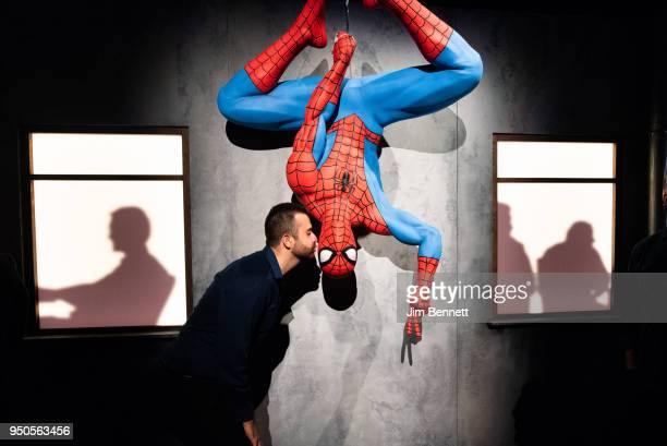 A patron pretends to kiss a model of SpiderMan on opening night of the Marvel Universe of Super Heroes exhibit at MoPop on April 20 2018 in Seattle...